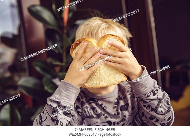 Little boy covering his face with a slice of white bread