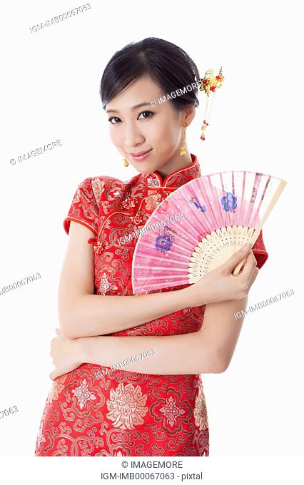 Young woman with cheongsam holding a fan and smiling at the camera
