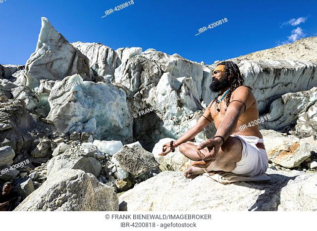 A Sadhu, holy man, is sitting in lotus pose, padmasana, on a rock at Gaumukh, the main source of the holy river Ganges, Gangotri, Uttarakhand, India