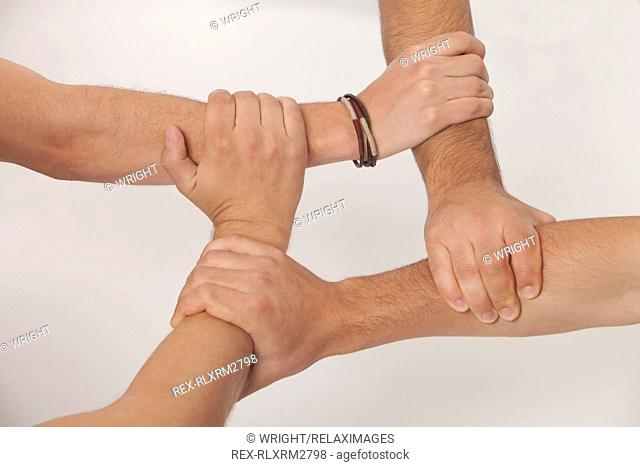 Hands linked holding teamwork four boys teenagers