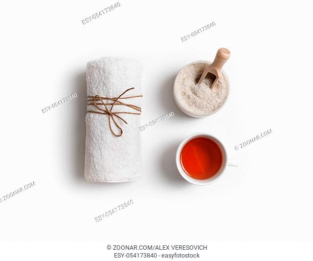 Towel, sea salt and tea cup on white paper background. Spa and beauty concept. Flat lay