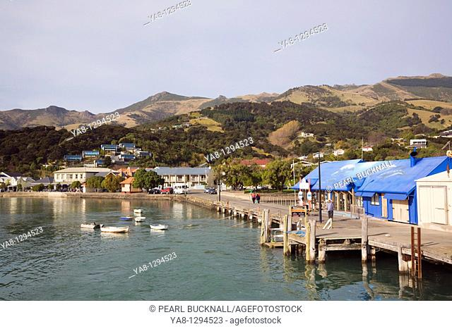 Akaroa Canterbury South Island New Zealand  Blue Pearl Centre building on main wharf in harbour in Bay with view to picturesque seaside resort town waterfront...