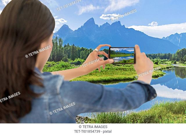 Young woman photographing mountain range