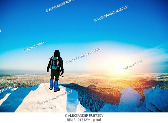 Hiker admiring view from snowy hilltop