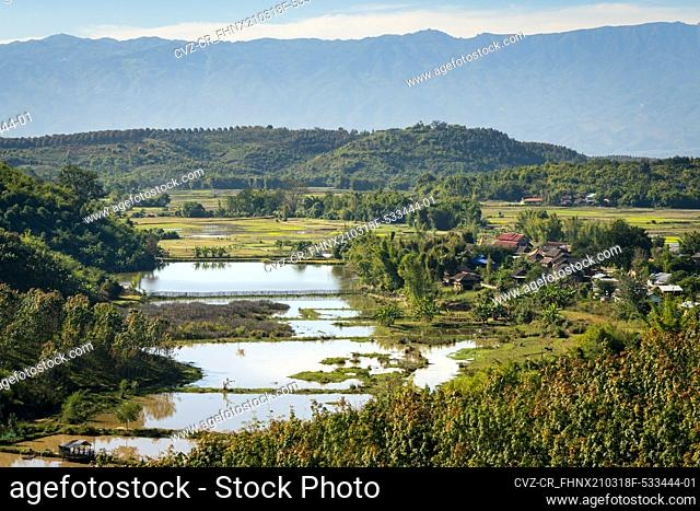 Scenic view of remote village next to flooded rice field, near Kengtung, Myanmar