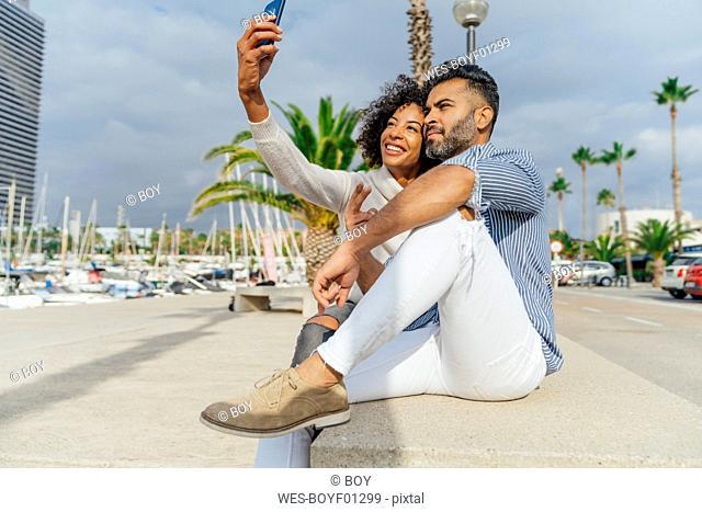 Spain, Barcelona, happy couple taking a selfie at the marina