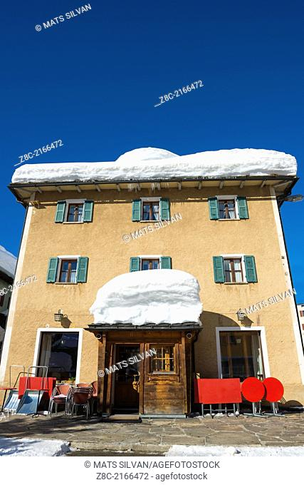 House with snow on the roof with blue sky in San Bernardino, Grisons Switzerland