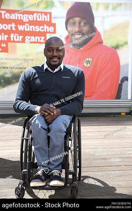 Alhassane BALDE, racing wheelchair driver, athlete, in front of the poster with his portrait, portrait, cropped single image, single motif