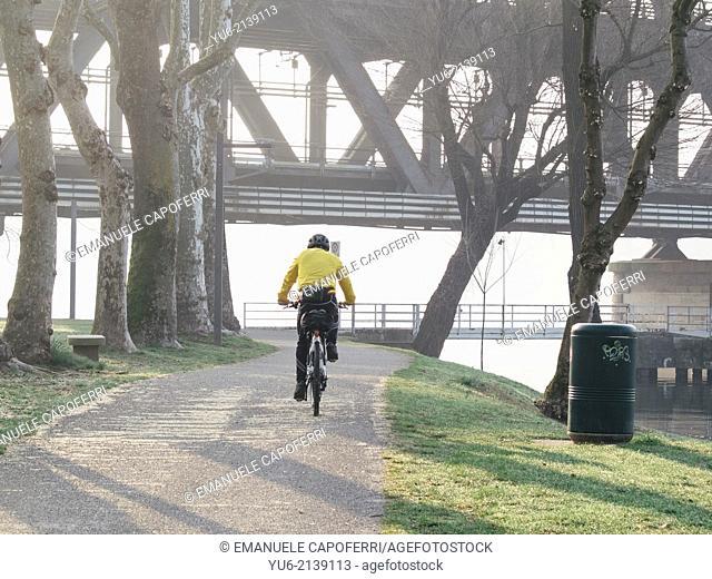 Iron bridge on Ticino river, cyclist on the bike path, Sesto Calende, Italy