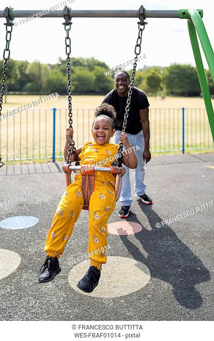 Father with happy daughter swinging on a playground