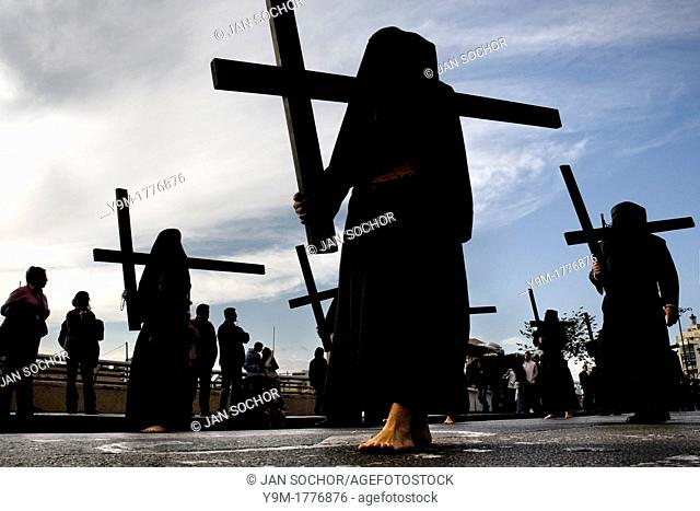 The Holy Week participants Nazarenos demonstrate their penance by carrying rough wooden crosses in the processions during the Easter celebration in Malaga