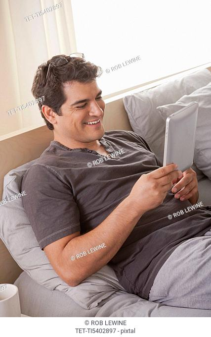 Young man laying on bed and using digital tablet