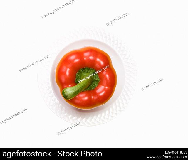 single red bell pepper on white plate isolated on white background