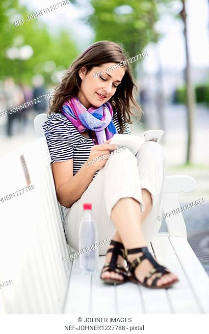 Young woman reading book on bench