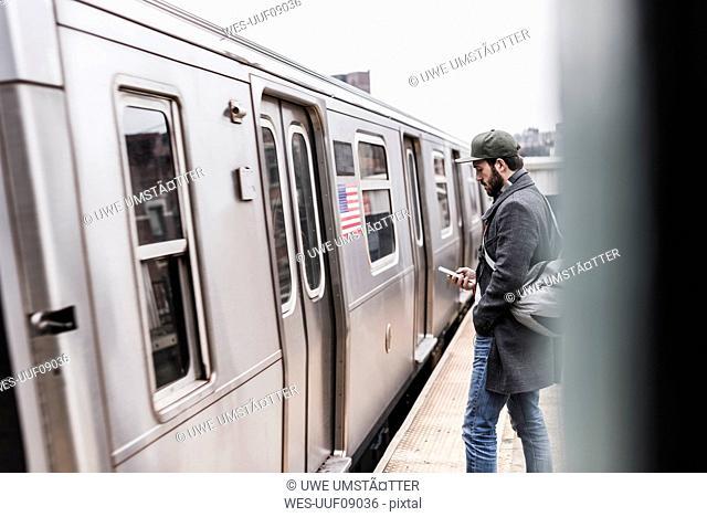 Young man waiting for metro at train station platform, using smart phone