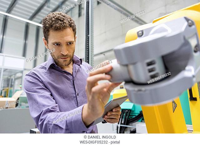 Technician adjusting industrial robot