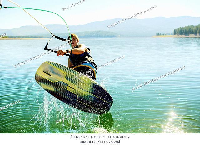 Caucasian man wakeboarding on lake