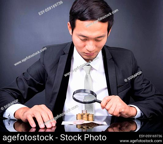 Businessman with magnifying glass looking With Stack Of Coins baht