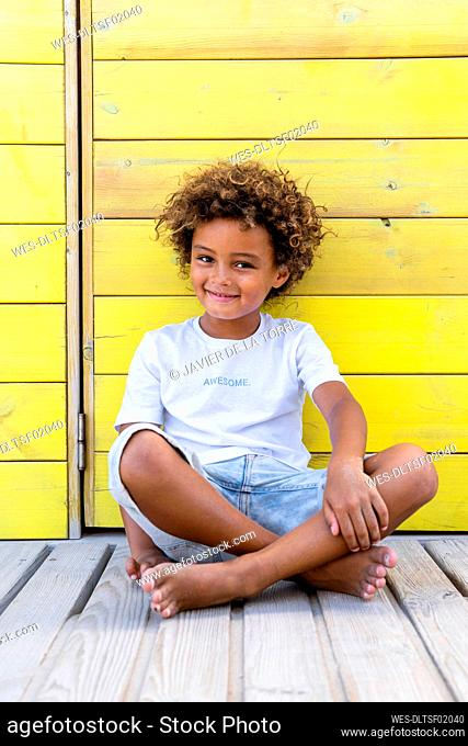 Cute smiling boy sitting on wooden walkway in front of yellow wall