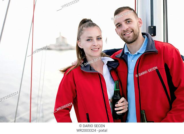 Young couple drinking beer on sailboat, Adriatic Sea
