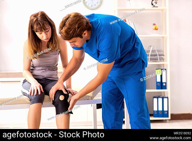 Young female patient visiting male doctor traumatologist