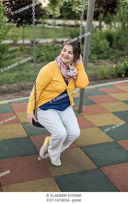 Smiling woman looking away while sitting on swing at playground