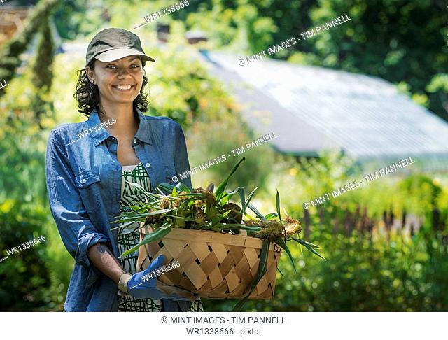 A young woman holding a large box of freshly cut vegetables
