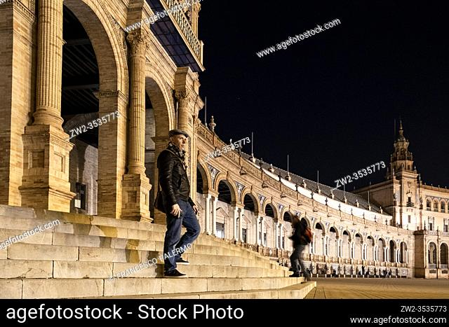 Boy looking forward in a plaza de espana at night. Seville, Andalusia. Spain