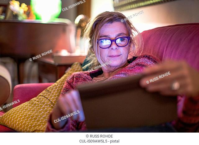 Mature woman wearing eye glasses reclining on sofa using digital tablet