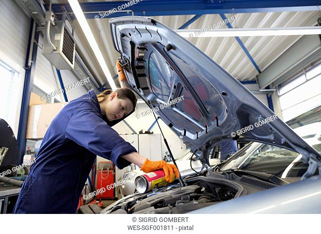 Young woman working in repair garage, checking engine