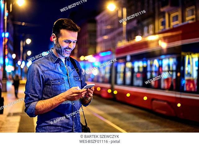 Smiling man with wireless headphones using smartphone while waiting for tram at night