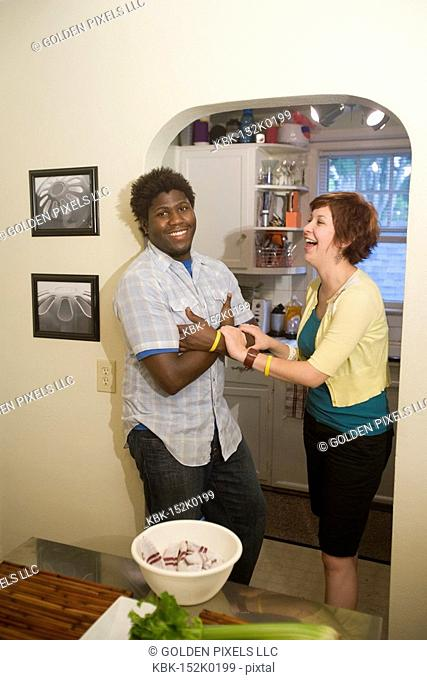 Portrait of a smiling young inter-racial couple outside their kitchen