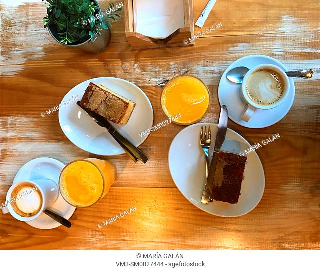 Breakfast: cups of coffee, cakes and glasses of orange juice. View from above