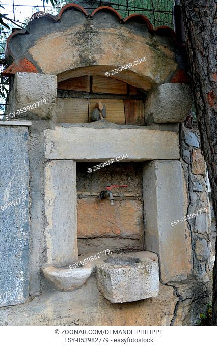Old stone fountain in the campaign on the Cretan