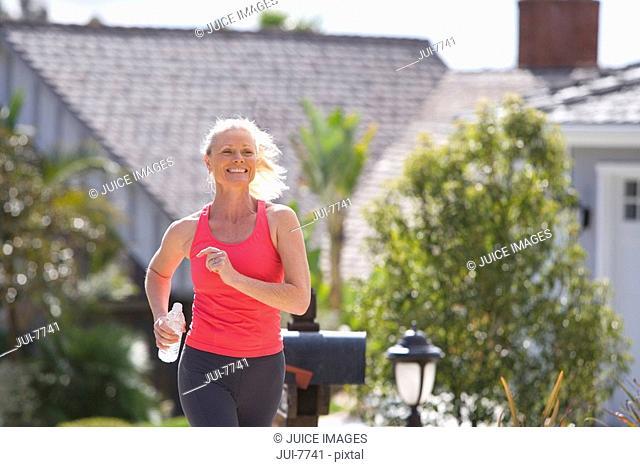 Active senior woman, in pink sports vest, jogging along suburban street, smiling