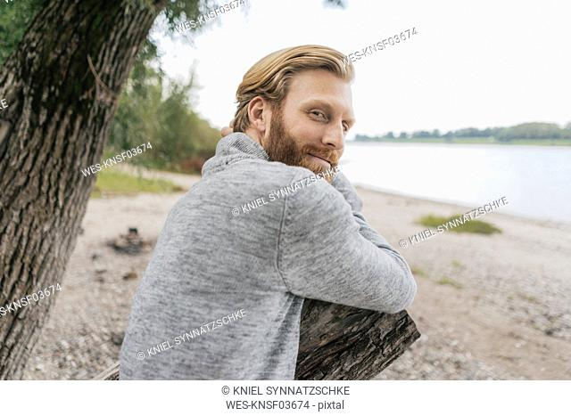 Germany, Duesseldorf, portrait of content man relaxing on the beach