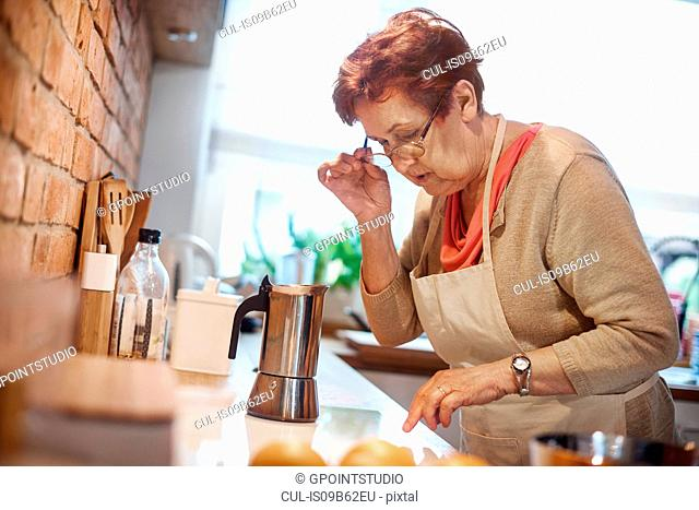 Senior adult woman learning to use electric hob to make coffee