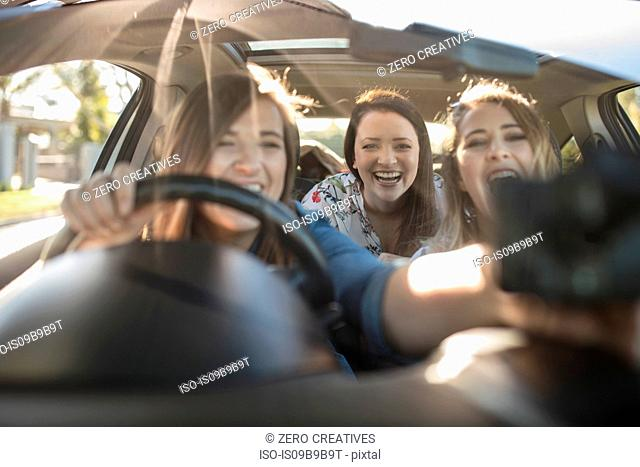 Three young women in car, driver adjusting sat nav on window