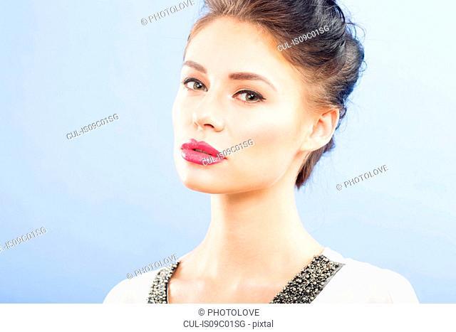 Beautiful young woman looking at camera, studio portrait