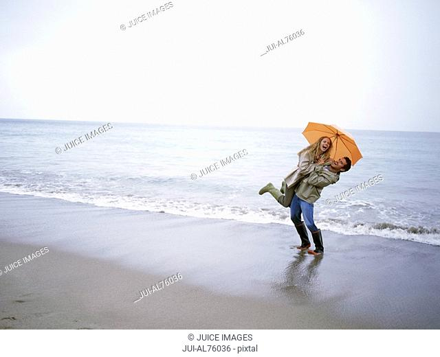 View of a man picking his girlfriend up on the beach