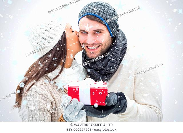 Attractive young couple in warm clothes holding gift against snow falling