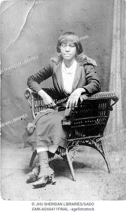 Full length seated portrait of young African American woman with neutral expression, wearing a light dress, dark coat and heeled boots, in elaborate chair, 1915