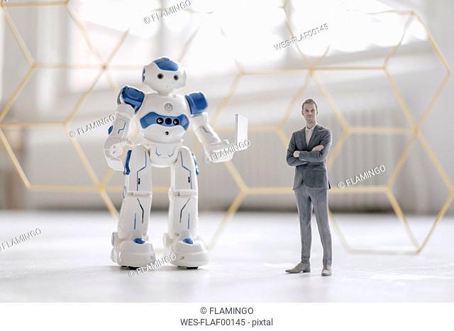 Miniature businessman figurine standing next to robot with laptop