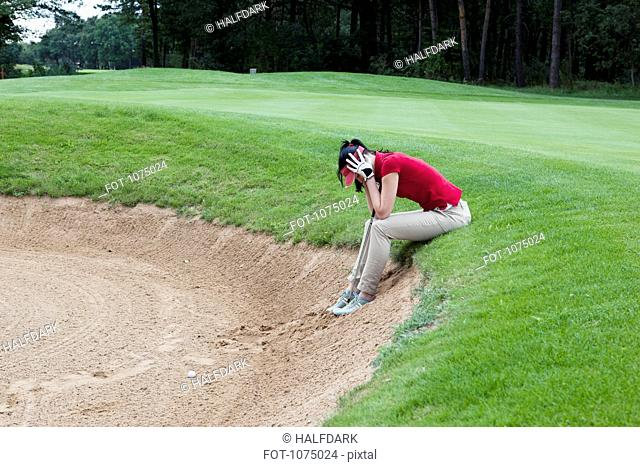 A female golfer sitting at the edge of sand trap, head in hands
