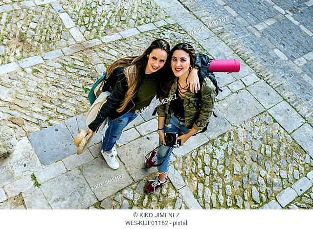 Two traveling young women standing on tow square