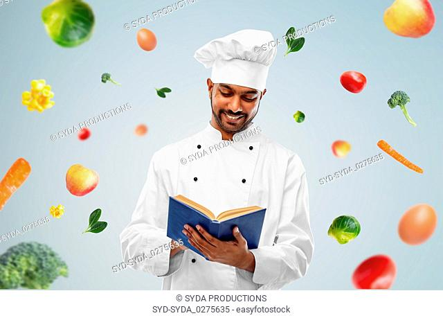 happy indian chef reading cookbook over vegetables