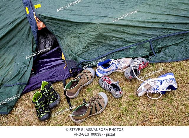 A 6 year old Japanese American boy peaks outside of his tent door that is littered with kids? sandals, and running shoes, in the primitive campsite