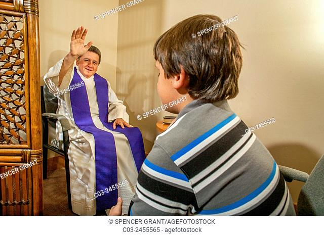 Sitting face to face, a priest gives absolution after hearing the confession of a boy parishioner at a Laguna Niguel, CA, Catholic church