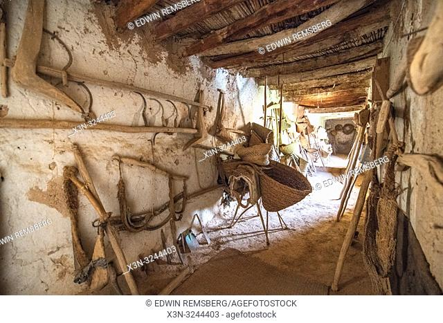 View down hallway of Muse de la Memoire Nomade with a variety of traditional farming equipment on display from the Berber nomads, Tighmert Oasis, Morocco