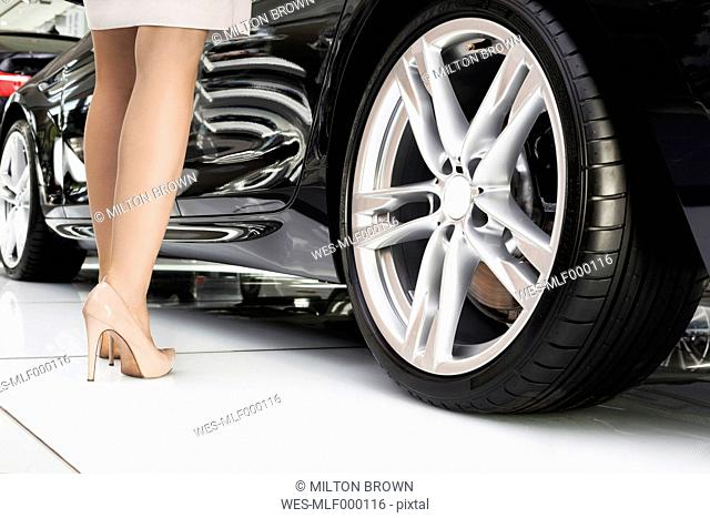 At the car dealer, Legs of a woman standing next to new car